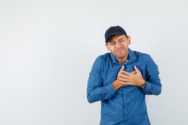 青いシャツ、キャップ、体調不良で心臓の痛みに苦しんでいる若い男。正面図。