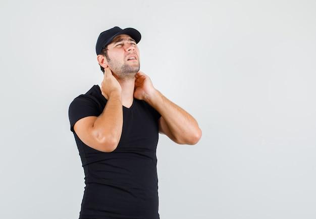 검은 티셔츠에 목 통증으로 고통받는 젊은 남자