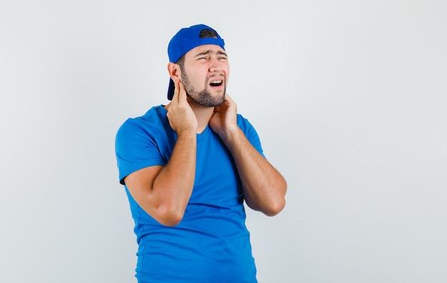 파란색 티셔츠와 모자에 목 통증으로 고통 받고 피곤해 보이는 젊은 남자
