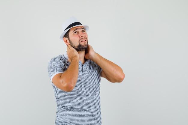 티셔츠, 모자에 목 통증으로 고통 받고 피곤한 젊은 남자. 전면보기.