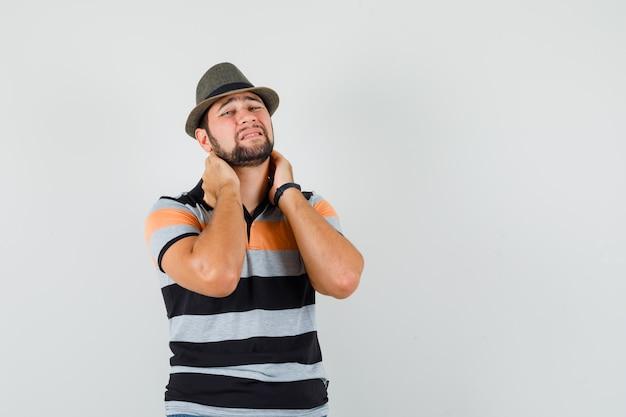 Giovane che soffre di dolore al collo in maglietta, cappello e sembra infastidito.