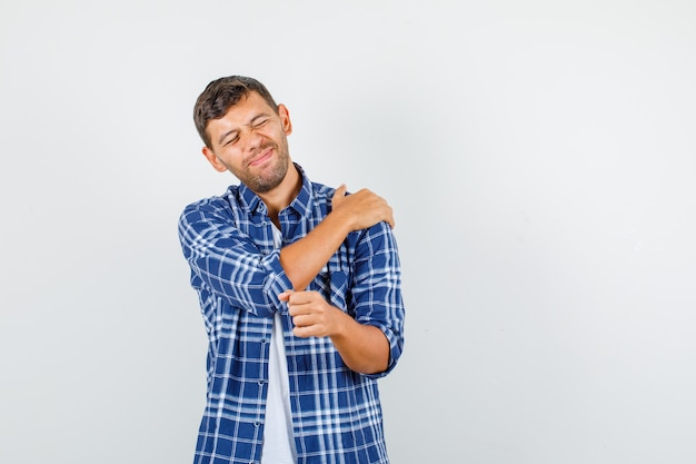 Young man suffering from pain in shoulder in shirt front view.