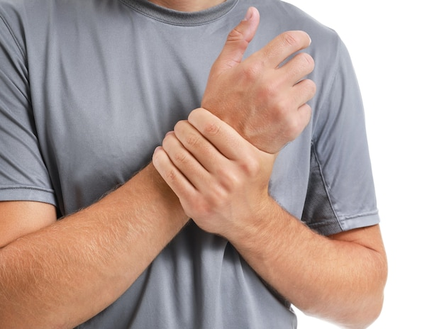 Young man suffering from pain in wrist isolated, closeup