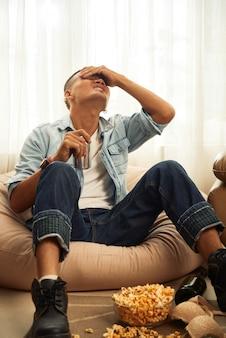 Молодой человек страдает от сильной головной боли утром после вечеринки и пьет из банки освежающего напитка