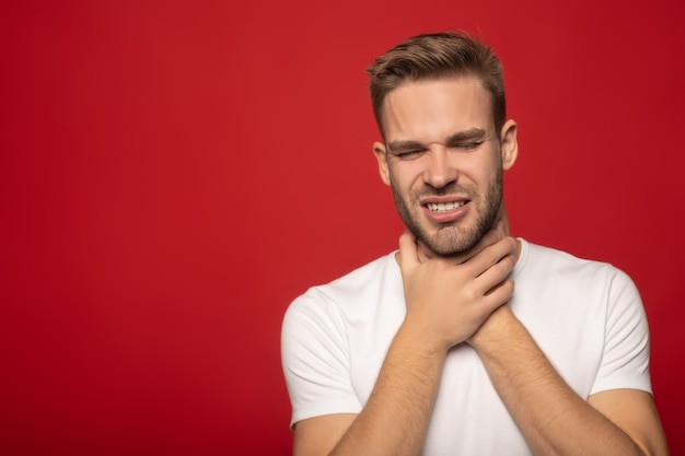 Young man suffering from soar throat isolated on red