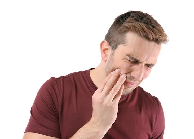 Молодой человек страдает от зубной боли, крупным планом