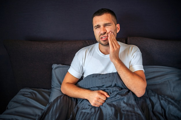 Young man suffering from toothache. he holds hand on cheek and keeps eyes closed. pain is terrible. he sits on bed. guy is covered with blanket.