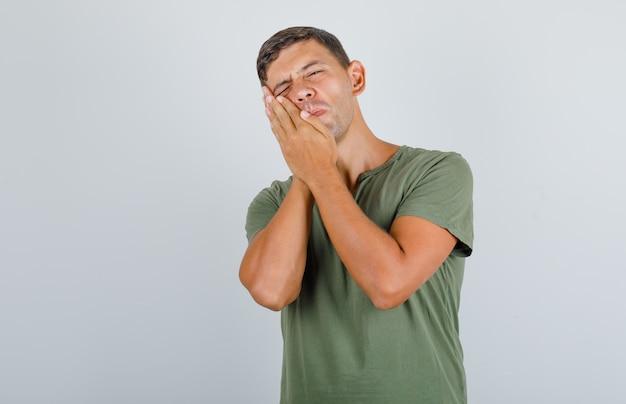 アーミーグリーンのtシャツで歯痛に苦しんで、痛みを伴う、正面を見て若い男。