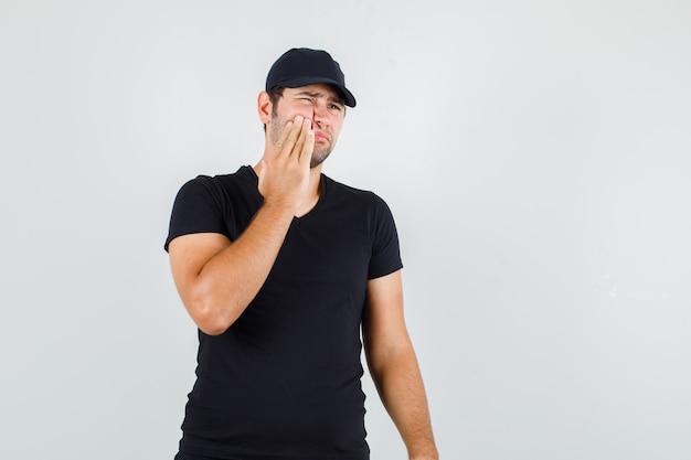 黒のtシャツで歯痛に苦しんでいる若い男