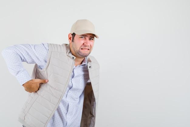 Молодой человек страдает от боли в пояснице в рубашке, куртке без рукавов, кепке и выглядит обеспокоенным, вид спереди.