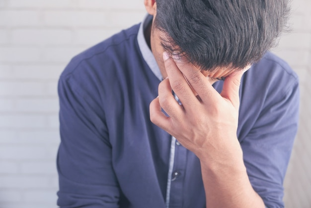 Young man suffering headache and covering his face with hand