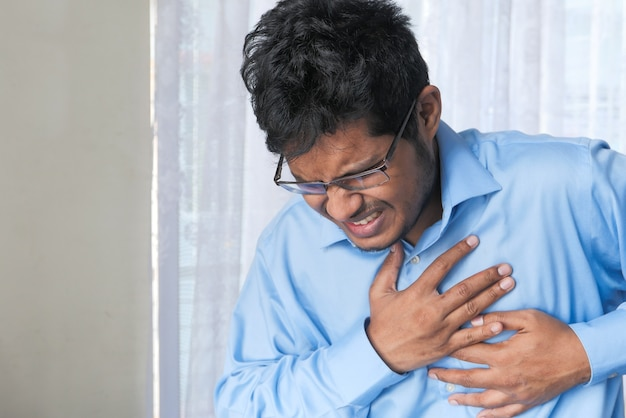 A young man suffering heart pain and holding his chest