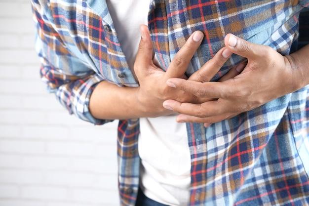 Молодой человек страдает от боли в сердце и держится за грудь рукой