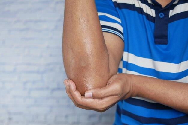 팔꿈치에 고통을 겪고 있는 젊은 남자