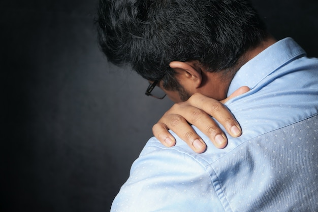 Young man suffering shoulder pain isolated on black.
