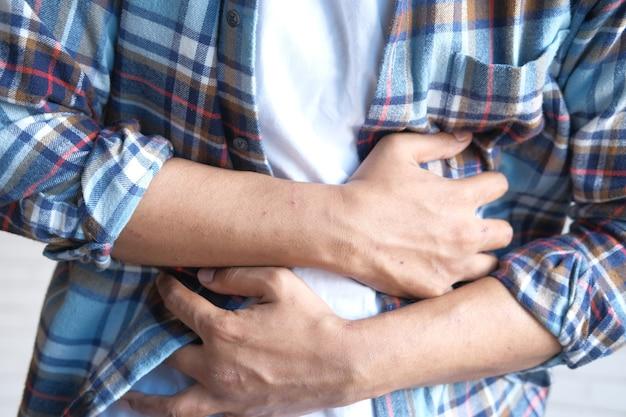 Молодой человек страдает от боли в животе крупным планом