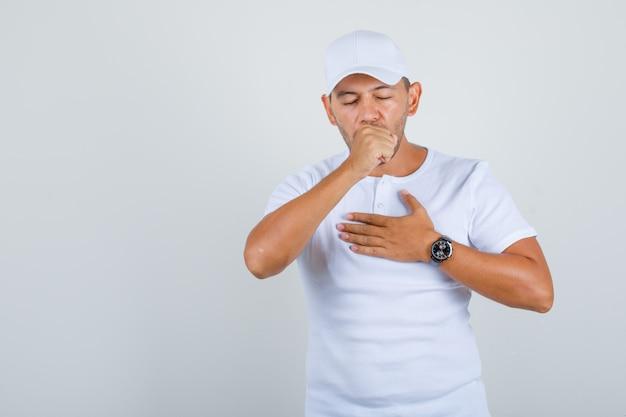 Молодой человек страдает от кашля в белой футболке, кепке и выглядит больным, вид спереди.