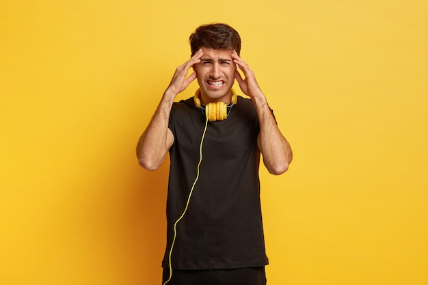 Young man suffers from headache, keeps hands on temples, clenches teeth from unpleasant feelings, dressed in black outfit, uses headphones