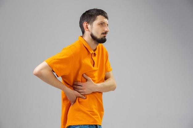 若い男は痛みに苦しんで気分が悪くなり、壁に衰弱が解消されます