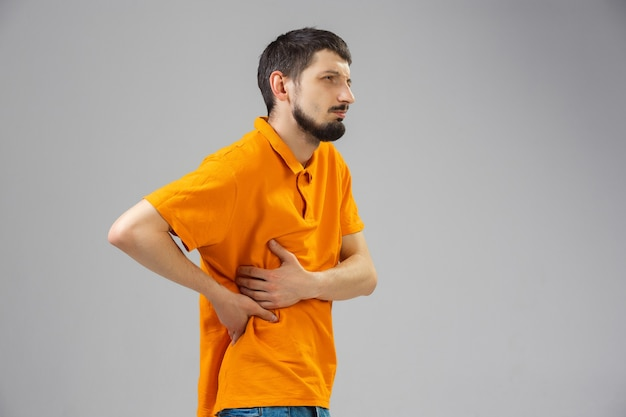 Young man suffers from pain feels sick ill and weakness isolted on wall