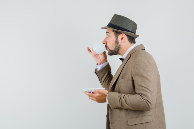 Young man in suit, hat drinking aromatic tea and looking focused .