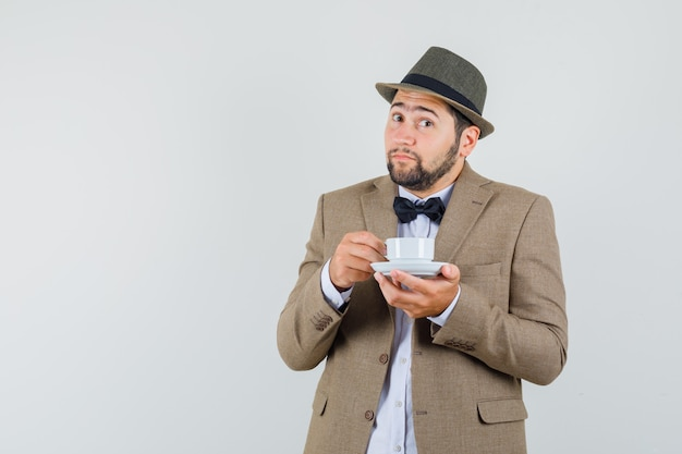 Young man in suit, hat drinking aromatic tea and looking positive , front view.