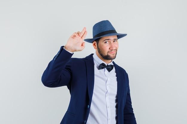 Giovane uomo in tuta, cappello gesticolando con due dita e guardando fresco, vista frontale.