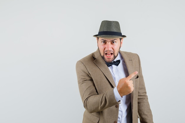 Young man in suit, hat shouting with finger up to the side and looking angry , front view.