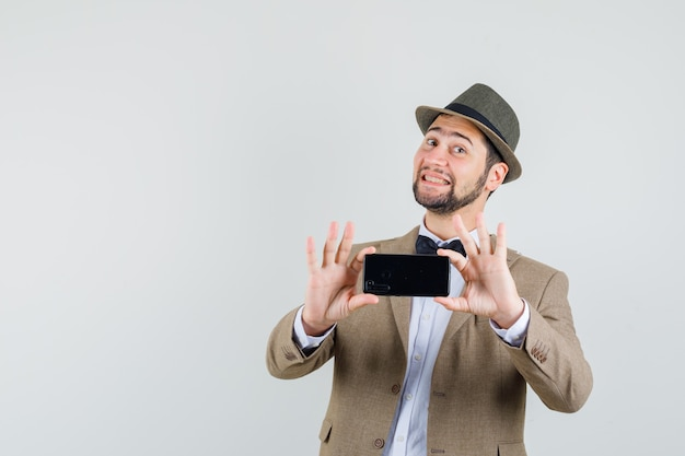 Young man in suit, hat taking photo on mobile phone and looking merry , front view.
