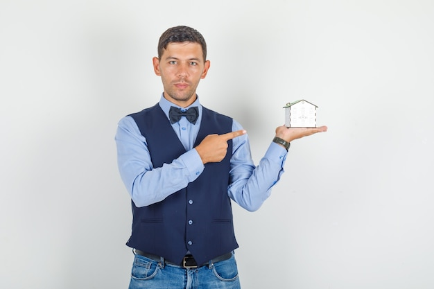 Young man in suit, jeans pointing finger at house model and looking hopeful