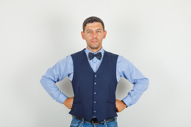Young man in suit, jeans standing with hands on waist and looking confident
