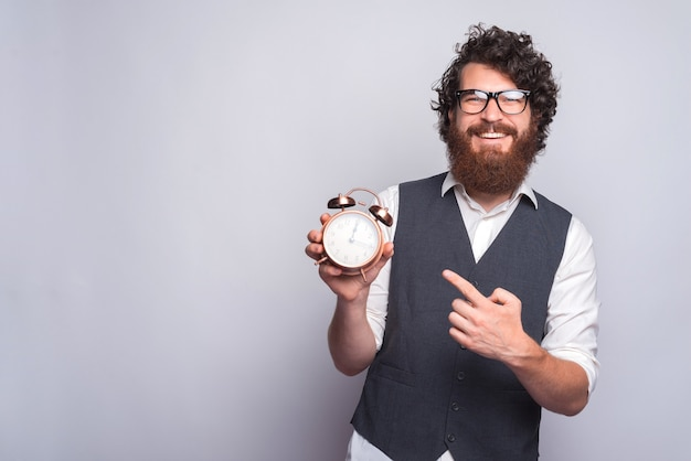 Young man in suit pointing at alarm clock on white.