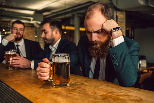 Young man in suit sit and sleep. he prop up head. guy hold beer mug. other two office workers sit behind and talk.
