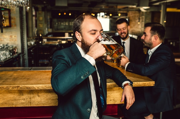 Young man in suit stand in bar and drink beer. two other men stand behind him. they talk.