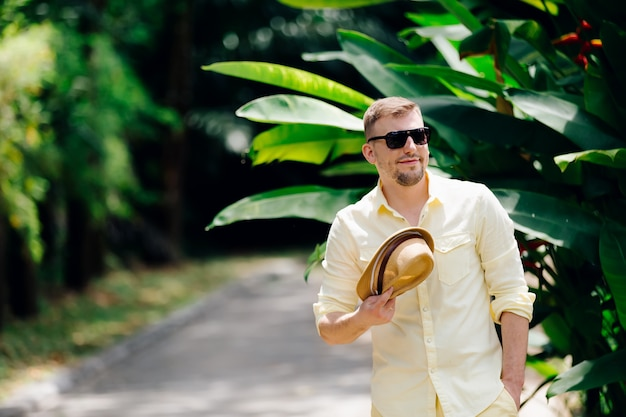 Young man in sunglasses casual clothes holding ylellow hat in hands having fun in sunny day. tropical background.