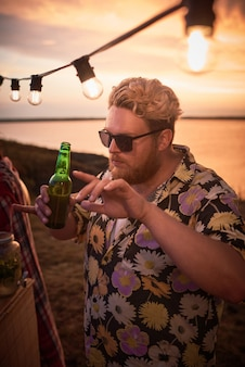 Young man in sunglasses drinking beer and dancing during a party on the beach