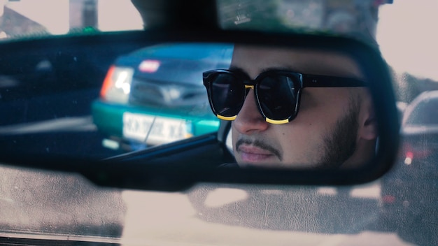 Young man in sunglasses driving car rear mirror view