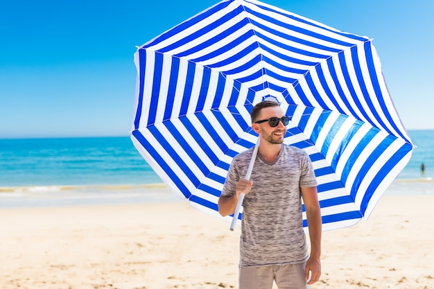 Young man in sunglasses walking on the beach with sun solar umbrella