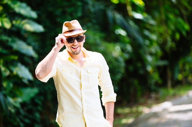 Young man in sunglasses wearing yellow hat and casual clothes having fun in sunny day. tropical background.