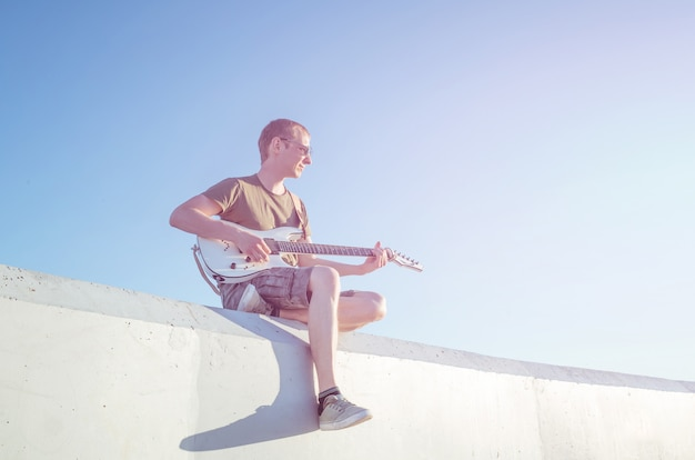 A young man in sunglasses with a guitar is sitting on the background of a cloudless sky.