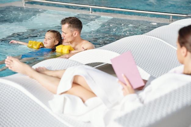 Молодой человек поддерживает свою маленькую дочь в защитных рукавах во время плавания в бассейне, проводя время в спа-центре на досуге