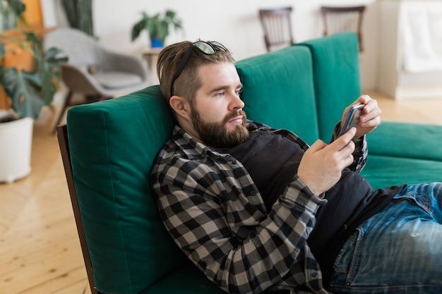 スマートフォンを使用してソーシャルネットワーキングサイトでサーフィンをしている若い男。テクノロジーとインターネットの概念。