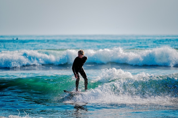 Молодой человек серфинг на волнах