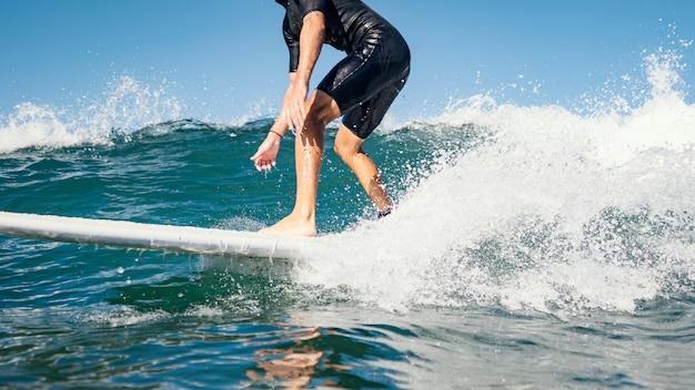 Молодой человек занимается серфингом на волнах океана с чистой водой