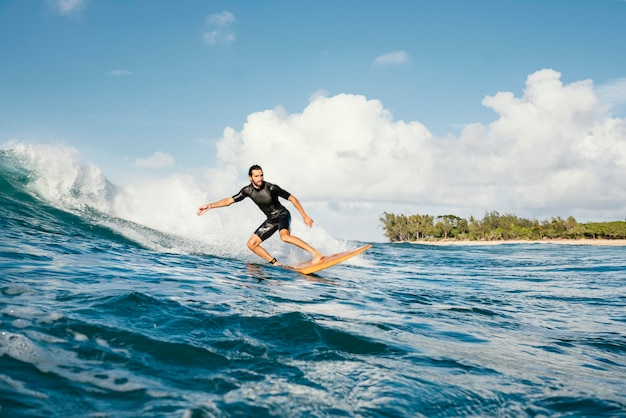 Young man surfs ocean clear water waves