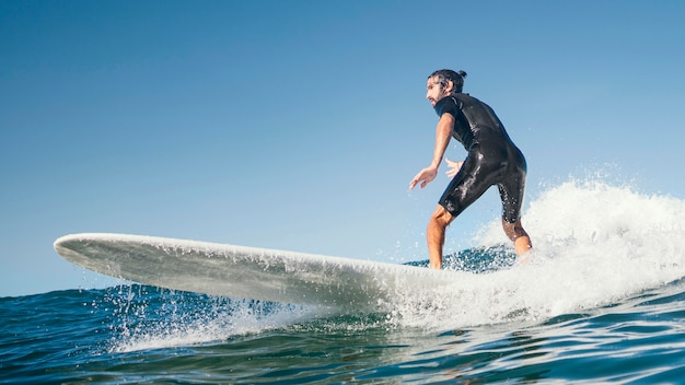 Young man surfs ocean waves