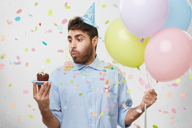 Young man surrounded by confetti holding cupcake and balloons