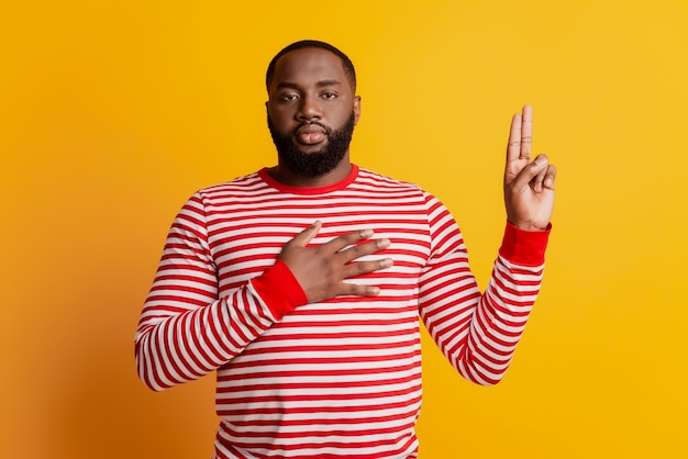 Young man swearing with hand on chest and fingers up serious face on yellow wall