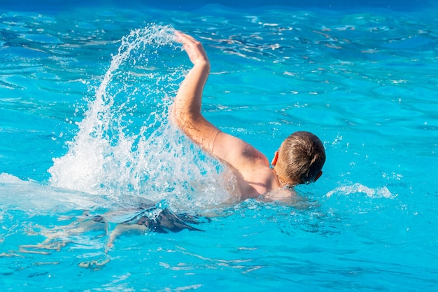 プールで泳いでいる若い男。リゾートで夏休み Premium写真