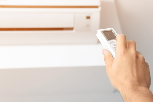 Young man switching on air conditioner at home